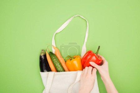 Photo pour Vue recadrée de la femme mettant des légumes colorés dans un sac de coton sur fond vert clair - image libre de droit