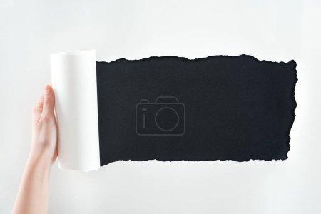 Photo pour Vue recadrée de femme retenant le papier blanc texturé avec le bord roulé sur le fond noir - image libre de droit