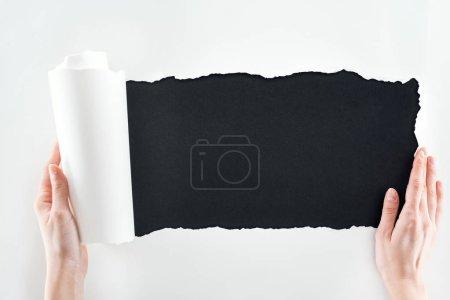 Photo pour Vue recadrée de femme retenant le papier blanc avec le bord roulé sur le fond noir - image libre de droit