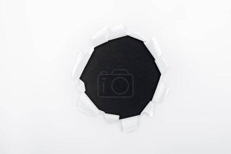 Photo pour Trou déchiqueté dans du papier blanc texturé sur fond noir - image libre de droit