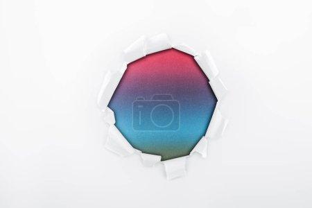 Foto de Agujero irregular en papel blanco texturizado sobre fondo multicolor - Imagen libre de derechos