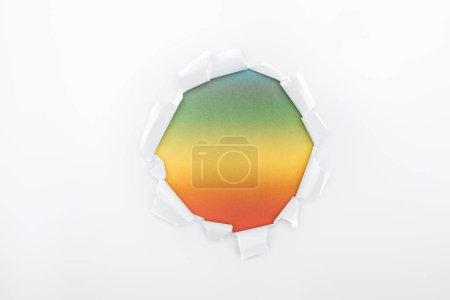 Photo pour Trou en lambeaux en papier blanc sur fond multicolore - image libre de droit
