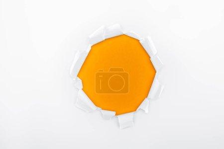 Photo pour Trou déchiqueté dans du papier blanc texturé sur fond orange - image libre de droit