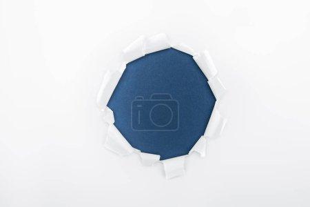 Foto de Agujero irregular en papel blanco texturizado sobre fondo azul oscuro - Imagen libre de derechos