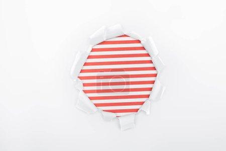 Photo pour Trou déchiré dans du papier blanc texturé sur fond rayé rouge - image libre de droit