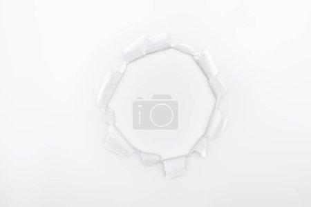Foto de Agujero irregular en papel texturizado sobre fondo blanco - Imagen libre de derechos