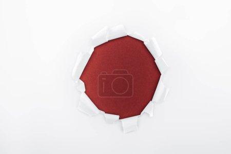 Photo pour Trou déchiqueté dans du papier blanc texturé sur fond bordeaux - image libre de droit