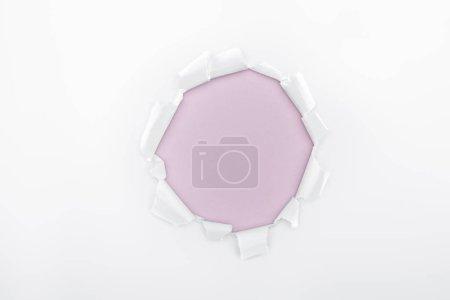 Photo pour Trou en lambeaux en papier blanc texturé sur fond violet clair - image libre de droit
