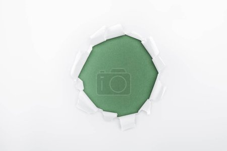 Photo for Ragged hole in textured white paper on green background - Royalty Free Image