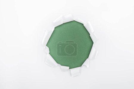 Photo pour Trou en lambeaux dans le papier blanc texturé sur fond vert - image libre de droit