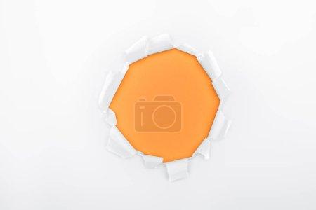 Photo pour Trou déchiré dans le papier blanc texturé sur le fond orange - image libre de droit