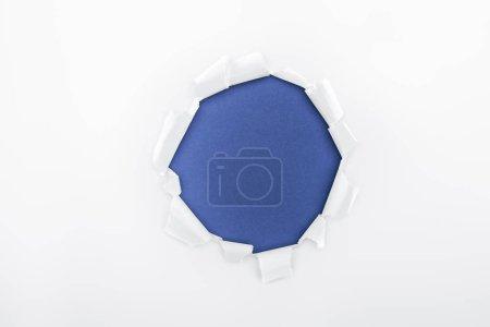 Photo pour Trou déchiré dans du papier blanc texturé sur fond bleu - image libre de droit