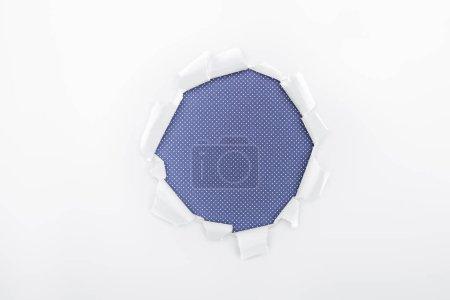 Photo pour Trou déchiré dans le papier blanc texturé sur fond bleu pointillé - image libre de droit