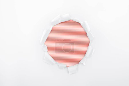 Foto de Agujero rasgado en papel blanco texturizado sobre fondo de rayas rojas - Imagen libre de derechos