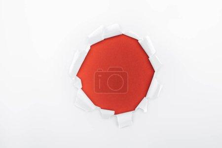 Photo pour Trou déchiré dans du papier blanc texturé sur fond rouge - image libre de droit