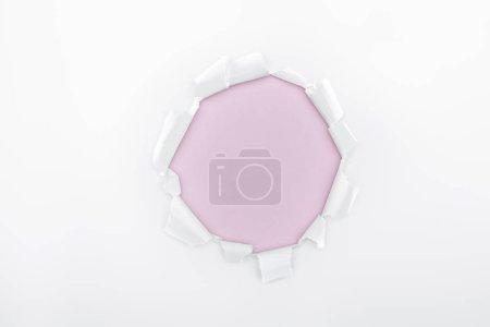 Foto de Agujero rasgado en papel blanco texturizado sobre fondo rosado - Imagen libre de derechos