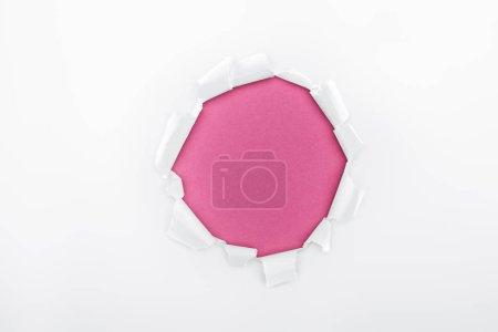 Foto de Agujero rasgado en papel blanco texturizado sobre fondo carmesí - Imagen libre de derechos