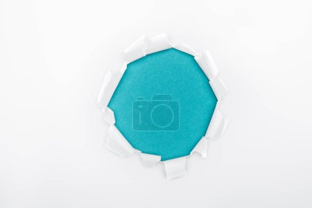Foto de Agujero irregular en papel blanco texturizado sobre fondo azul - Imagen libre de derechos