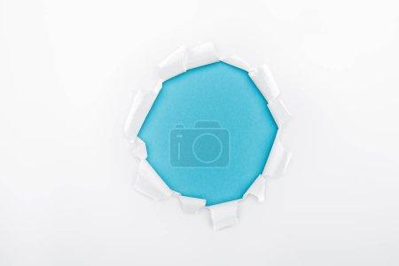 Photo pour Trou en lambeaux dans du papier texturé blanc sur fond bleu - image libre de droit