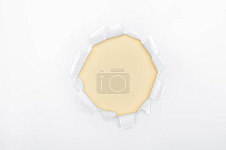 Foto de Orificio roto en papel blanco texturizado sobre fondo marfil - Imagen libre de derechos
