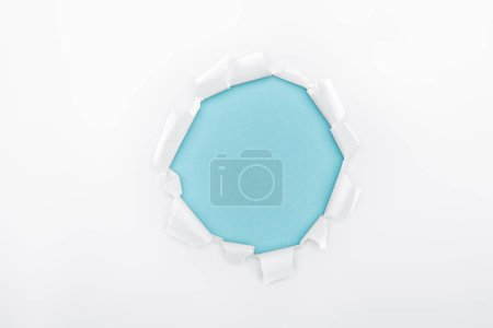 Photo for Torn hole in textured white paper on blue background - Royalty Free Image