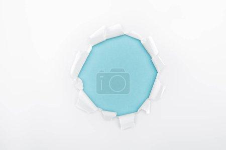 Foto de Agujero desgarrado en papel blanco texturizado sobre fondo azul - Imagen libre de derechos
