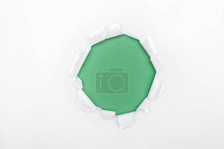 Photo pour Trou déchiré dans du papier texturé blanc sur fond vert - image libre de droit