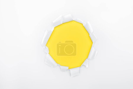 Photo for Torn hole in white textured paper on yellow background - Royalty Free Image