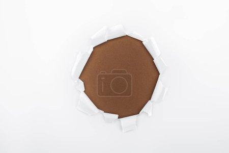 Foto de Agujero roto en papel blanco texturizado sobre fondo marrón - Imagen libre de derechos