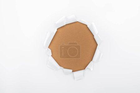Foto de Agujero rasgado en papel blanco texturizado sobre fondo marrón - Imagen libre de derechos