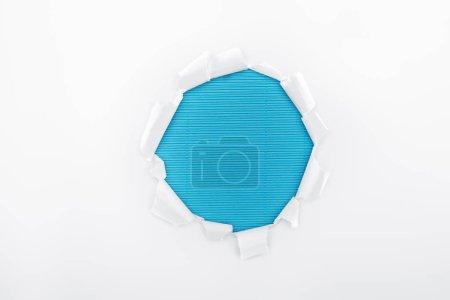 Photo pour Trou déchiré dans du papier texturé blanc sur fond rayé bleu - image libre de droit