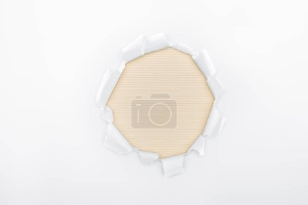 Photo for Ripped hole in white textured paper on beige striped background - Royalty Free Image