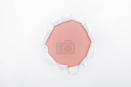 Photo pour Trou déchiré en papier texturé blanc sur fond rayé rouge - image libre de droit