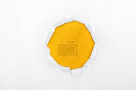 Photo pour Trou déchiré en papier texturé blanc sur fond rayé orange - image libre de droit