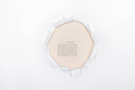 Photo pour Trou déchiré en papier texturé blanc sur fond Ivoire - image libre de droit