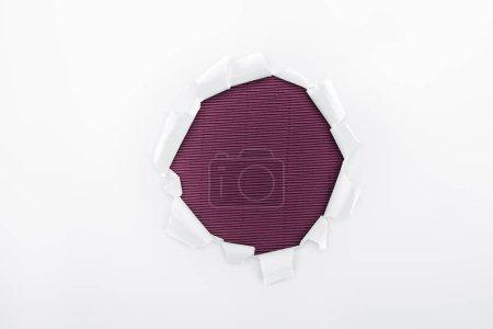 Photo pour Trou déchiré dans du papier texturé blanc sur fond violet - image libre de droit