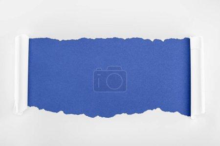 Photo pour Papier blanc texturé Ragged avec des bords de courbure sur le fond bleu - image libre de droit