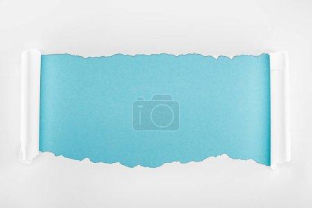 Photo pour Papier blanc déchiré avec bords bouclés sur fond bleu clair - image libre de droit