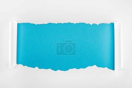 Photo pour Papier blanc déchiré avec des bords de courbure sur le fond bleu - image libre de droit