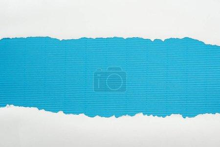 Photo pour Papier texturé blanc déchiré avec espace de copie sur fond rayé bleu - image libre de droit