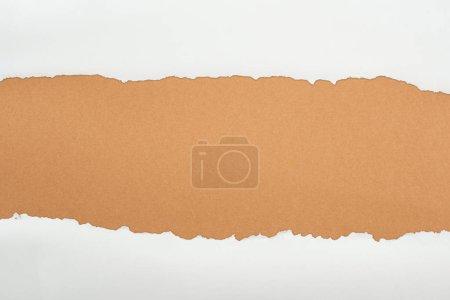 Foto de Papel de textura blanca rasgado con el espacio de copia sobre fondo marrón - Imagen libre de derechos