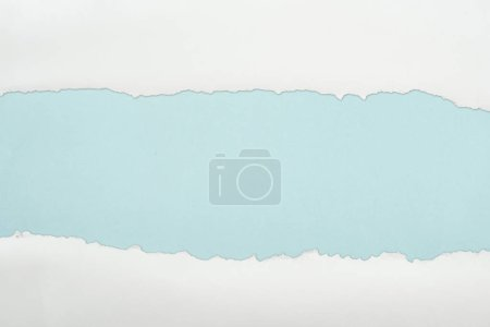 Foto de Papel con textura blanca rasgada con espacio de copia en fondo azul claro - Imagen libre de derechos