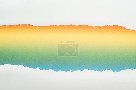 Photo pour Papier texturé blanc déchiré avec espace de copie sur fond multicolore - image libre de droit