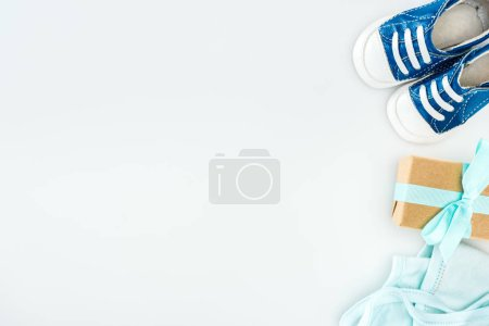 Photo for Top view of blue sneakers, gift box and bonnet on white background with copy space - Royalty Free Image