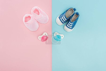 Photo for Top view of pacifiers, booties, sneakers on pink and blue background with copy space - Royalty Free Image