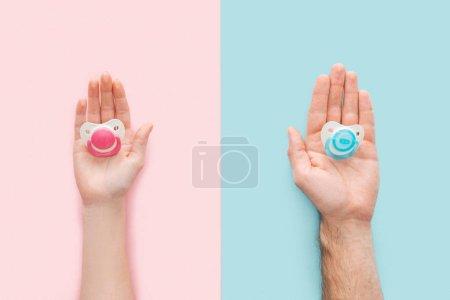Photo pour Vue partielle de la femme et de l'homme tenant des sucettes sur fond bleu et rose - image libre de droit