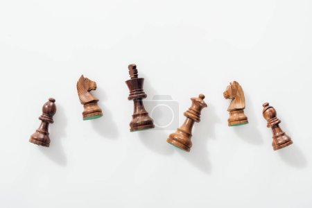 Photo for Top view of wooden brown chess figures on white background - Royalty Free Image