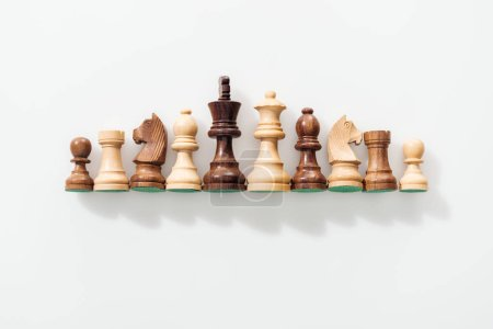 Photo for Top view of row made of brown and beige wooden chess figures on white background - Royalty Free Image
