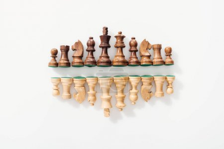 Photo for Top view of rows made of brown and beige wooden chess figures on white background - Royalty Free Image