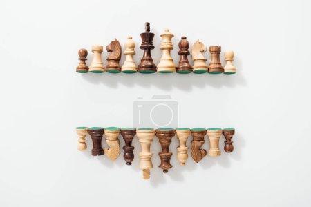 Photo pour Vue de dessus de lignes, de figures d'échecs en bois sur un fond blanc avec espace de copie - image libre de droit